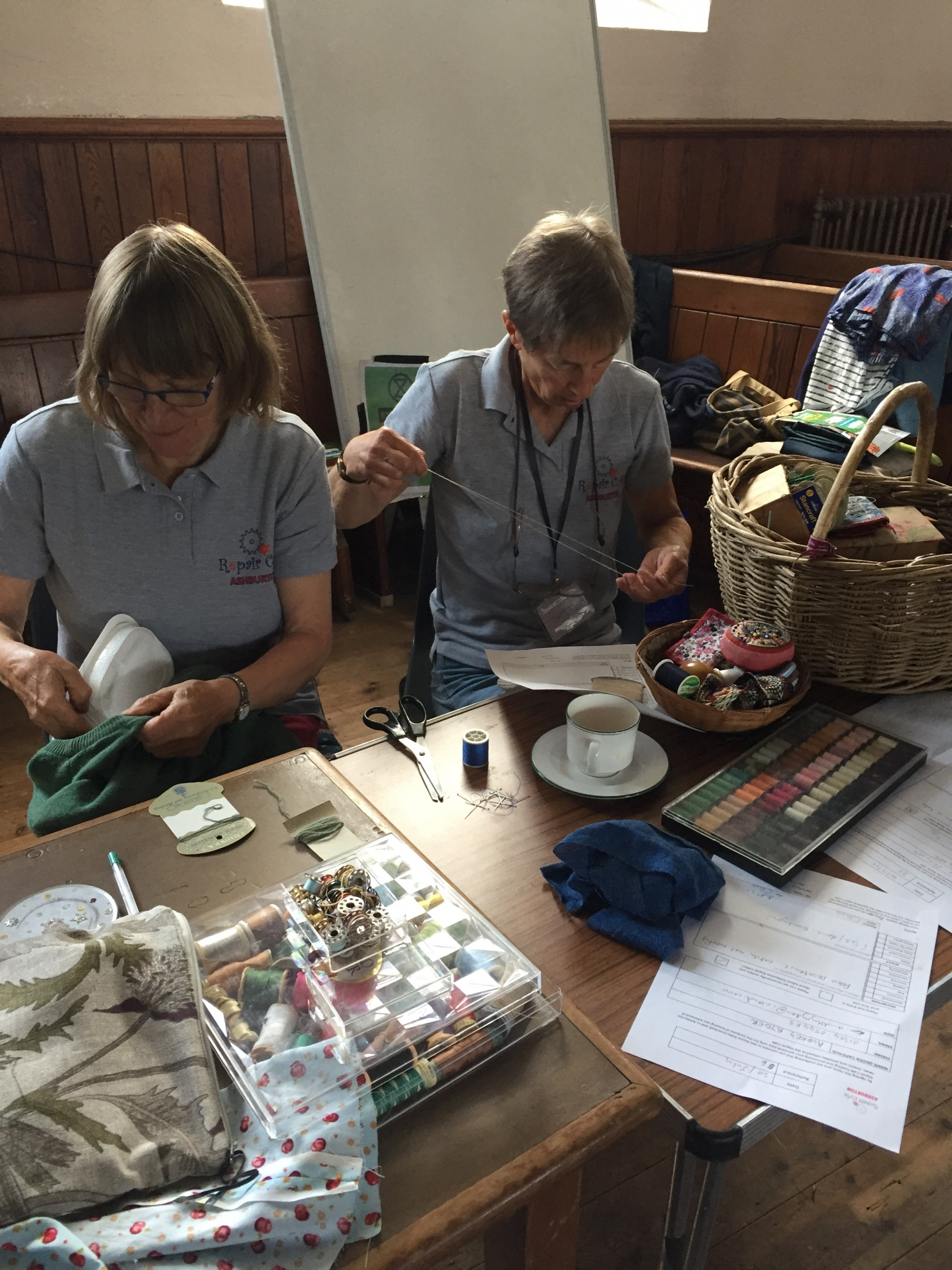 Two repair cafe volunteers at a table sewing.