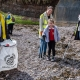 Adults and children litter picking on beach.
