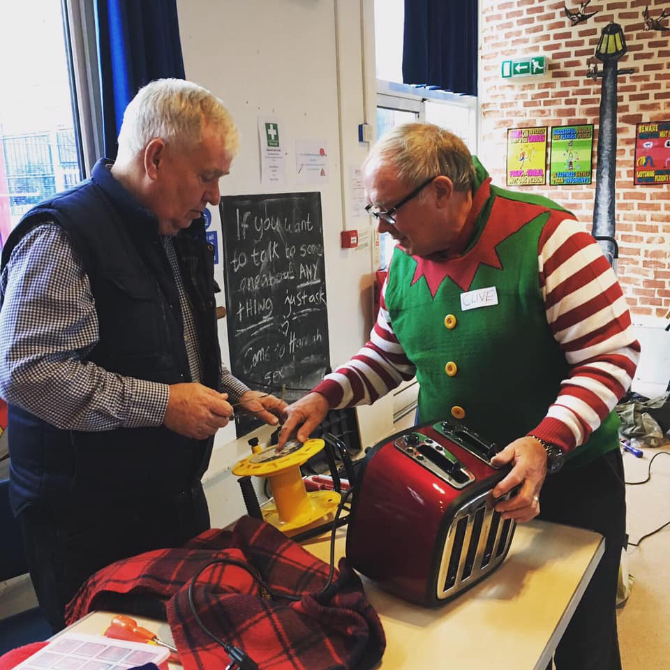 A man in an elf costome taking a look at a toaster that needs mending