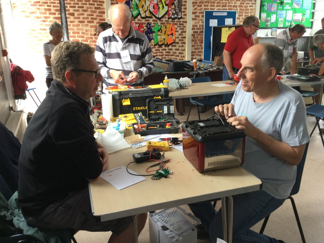 A volunteer and visitor sit at a table while the volunteer fixes a toaster