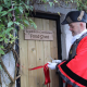 Mayor in tradiational black hat and red coat cutting the ribbon on the food shed door