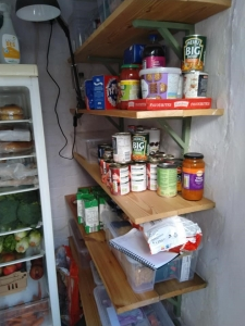 Shelves with fresh produce, dried goods and tinned groceries