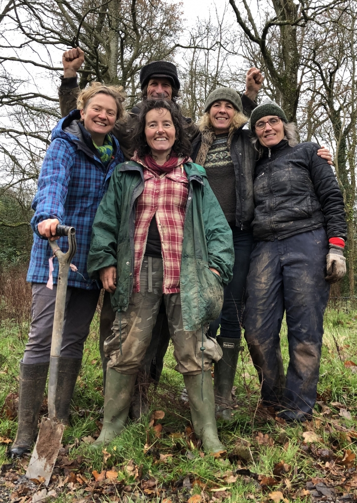 A small group of people wrapped up warm and muddy, one with a spade in her hand